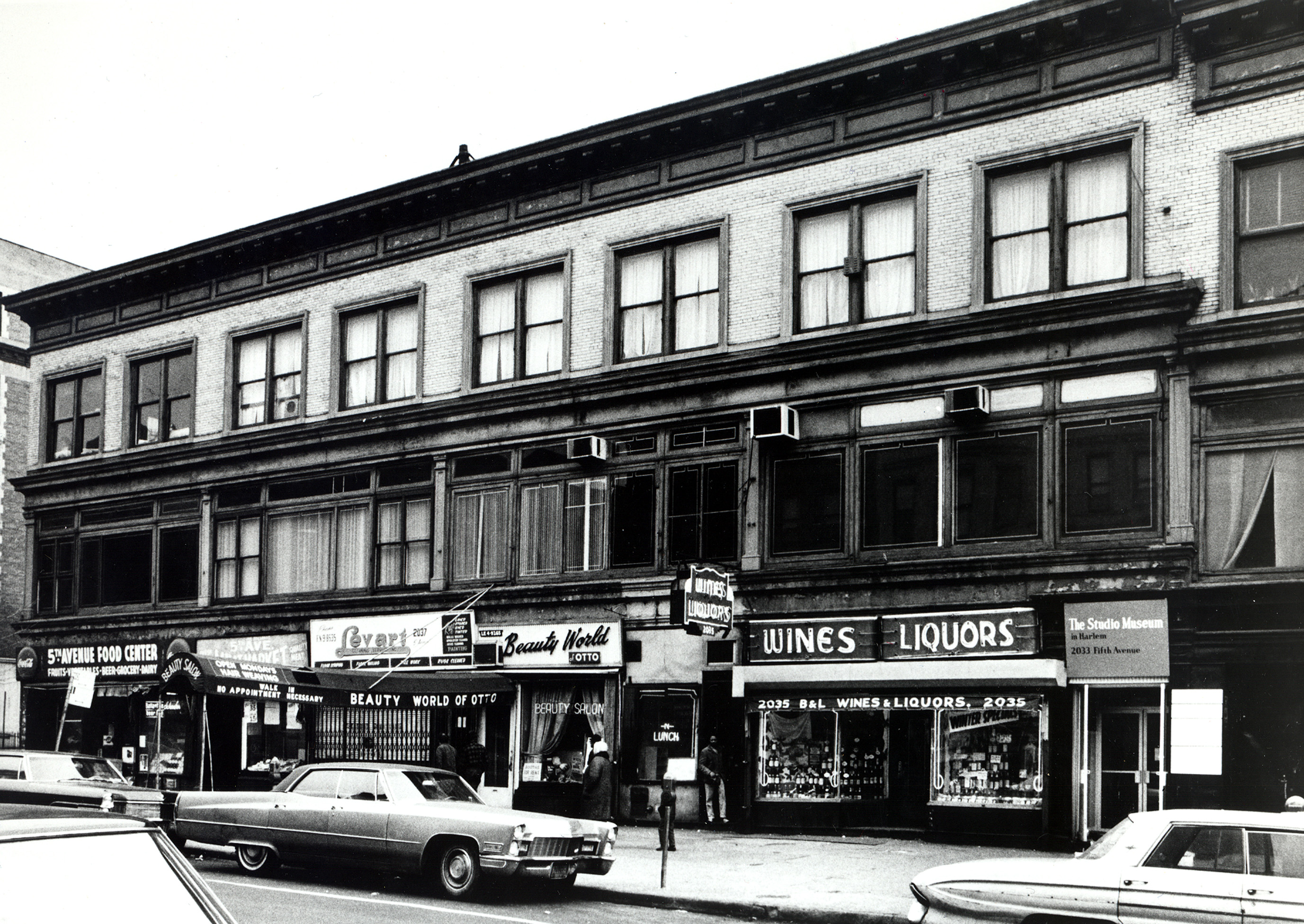 A black and white photograph of Harlem storefronts and The Studio Museum's first location in the late '60s.