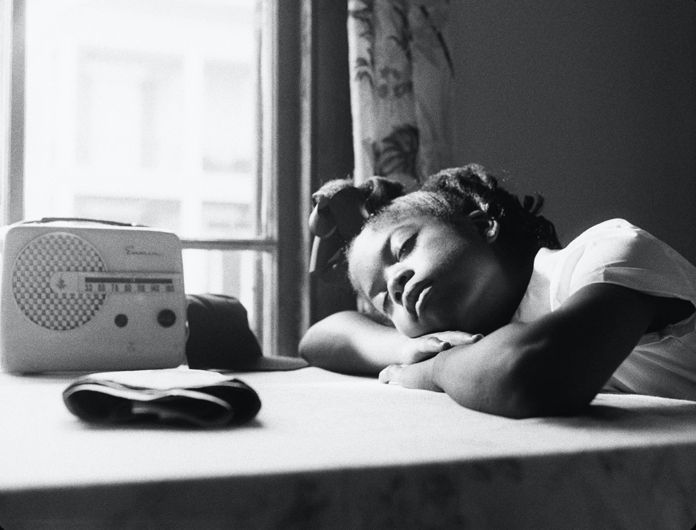 A black-and-white image of a young Black schoolgirl resting in the sunlight from a bright window with an old-time radio.