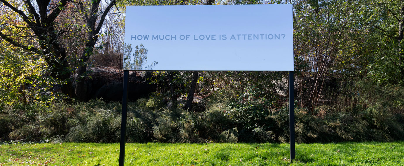 A mirrored billboard with the words How Much of Love is Attention? displayed in a park