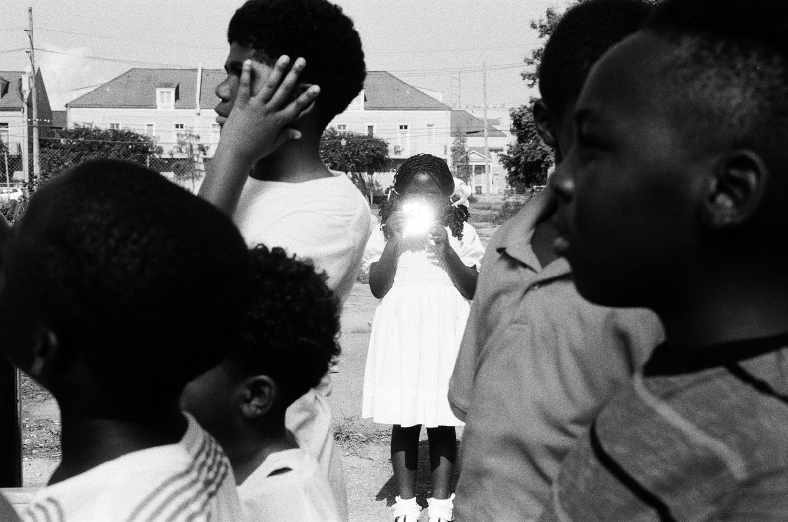 A black-and-white image of a young Black girl in a white dress