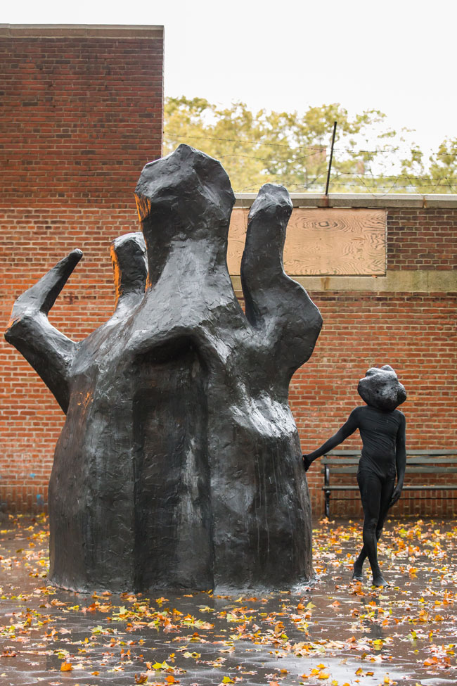 A figure all in black wearing a mask touches the black sculpture
