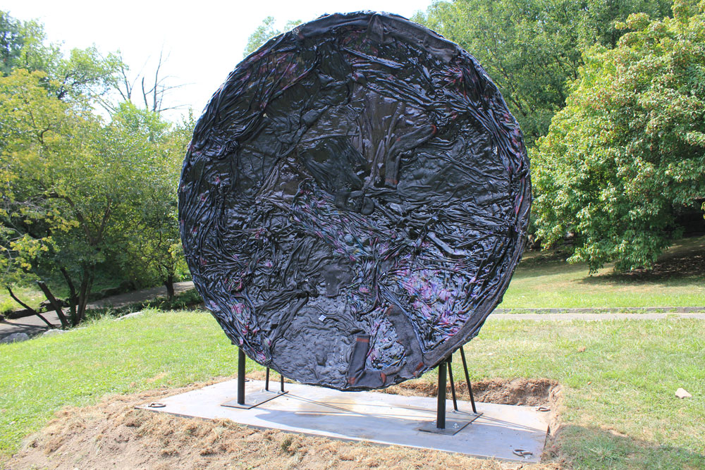 Textured plate shape sculpture on pedestal in a park