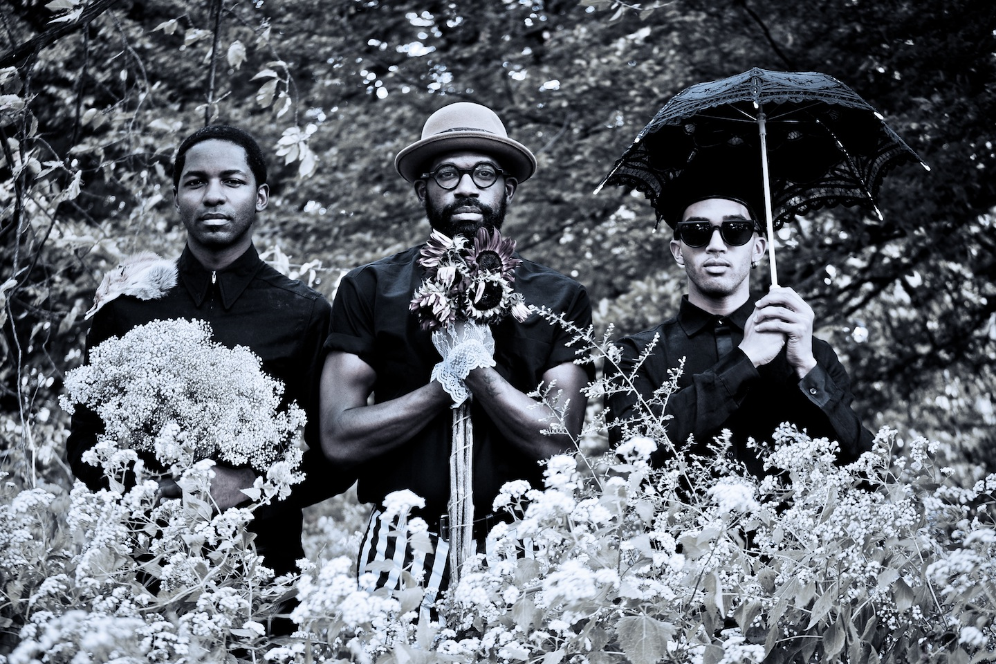 A black and white portrait of three black men standing side by side with gloved hands two are holding bouquets while one holds an umbrella.