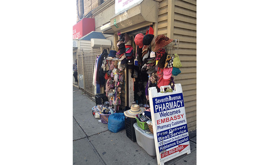 The exterior of a clothing bodega with hanging hats and clothing, with a blue and white sign for a nearby pharmacy