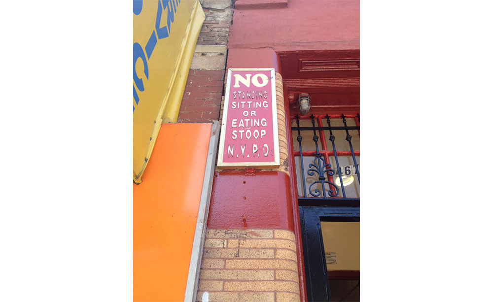 A read and white sign that says no standing, sitting, or eating stoop NYPD.