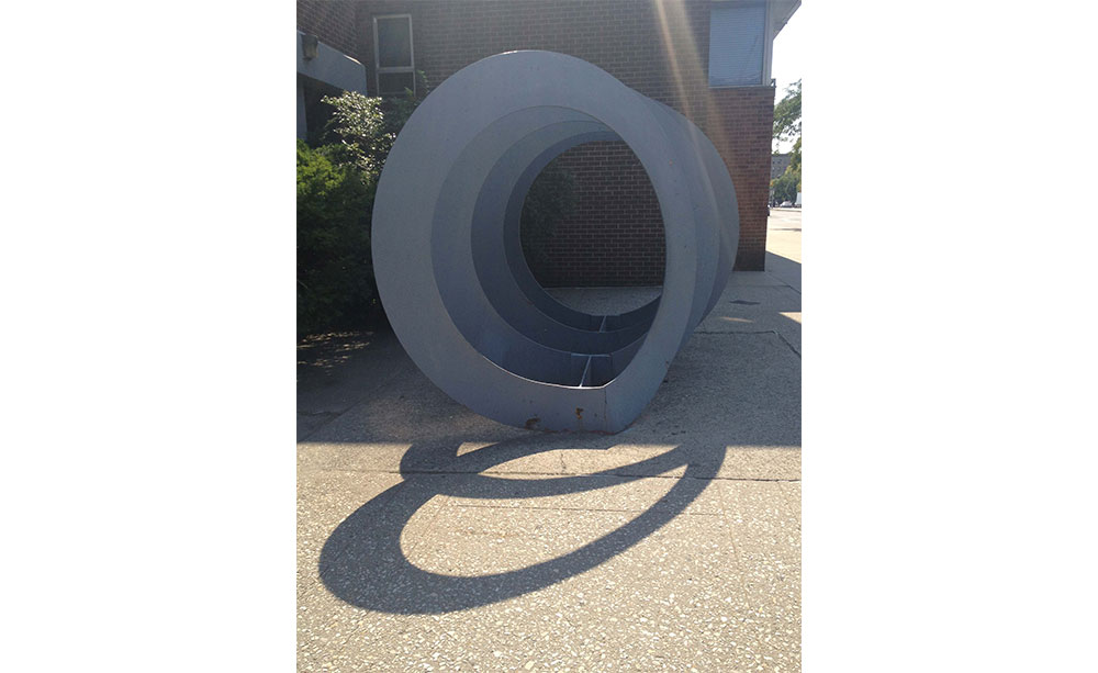 Sculpture made of large steel rings in a row, which project a shadow in the bright sun.
