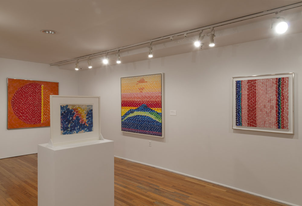 Installation of Alma Thomas works at the Studio Museum in Harlem. On display are three brightly colored works on the wall, and one smaller work displayed on a podium.