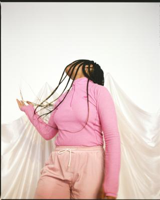 Artist E. Jane tilts head back while using her hand to flip their long braids.