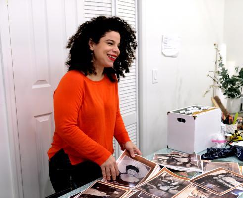 Portrait of Firelei Báez standing with photographs