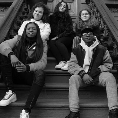 A group of teens sitting on a Harlem brownstone front stoop