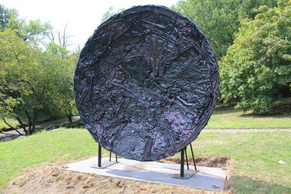 Textured plate shape sculpture on pedestal in a park
