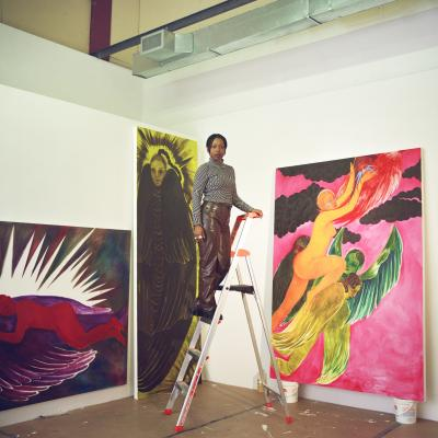 Naudline Pierre standing on a ladder in her studio
